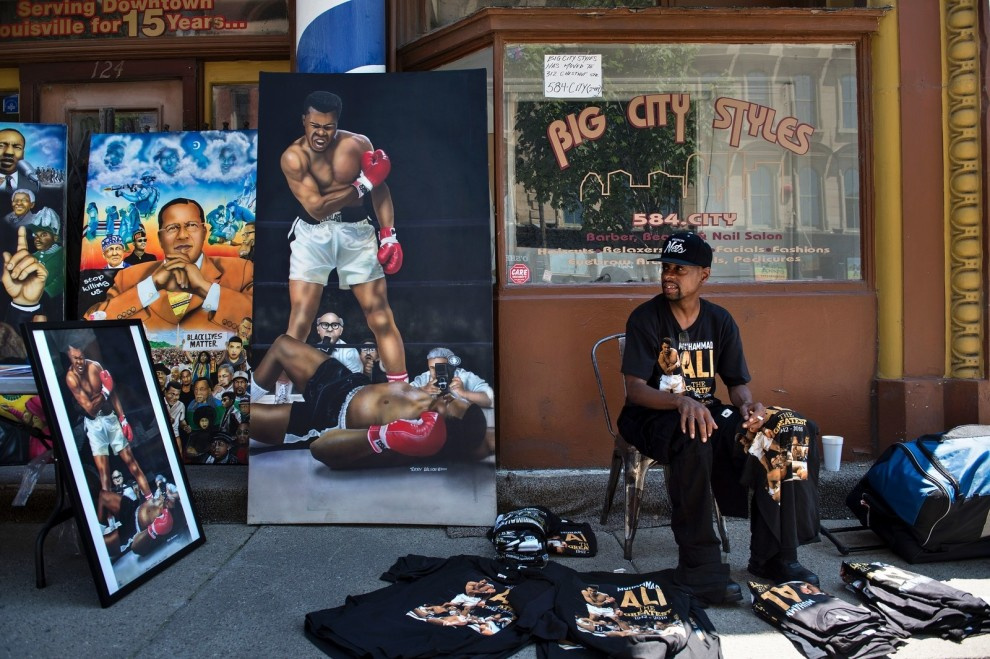 A vendor sells Muhammad Ali memorabilia while people attend a memorial service for the boxing legend at the KFC Yum! Center nearby on June 10 in Louisville.