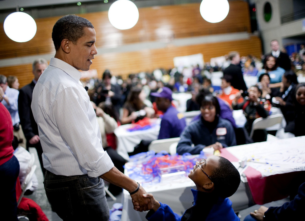 President Obama greets a boy at Calvin Coolidge High School, Washington, D.C., as students, military families, and volunteer service groups work on various projects supporting troops, Jan. 19, 2009.